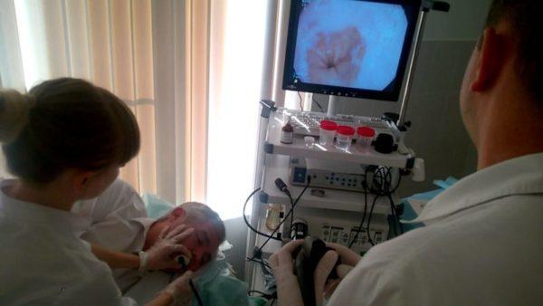 Медсестра помогает вставить шланг прибора и держит пациента за руки